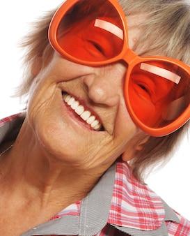 Senior donna che indossa grandi occhiali da sole facendo azione funky isolato su sfondo bianco