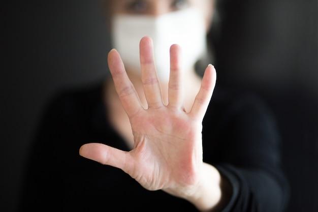 La maschera d'uso della donna senior, mostra le mani pulite e mostra le mani di arresto. messa a fuoco selettiva.