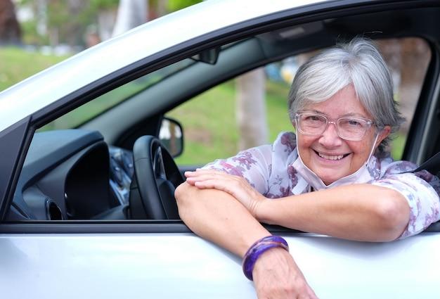 Donna anziana che indossa una maschera chirurgica a causa del coronavirus seduta all'interno dell'auto parcheggiata guardando la fotocamera. sorridente donna anziana dai capelli grigi indossando occhiali