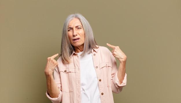 Senior donna con un cattivo atteggiamento che sembra orgogliosa e aggressiva, rivolta verso l'alto o facendo segno divertente con le mani