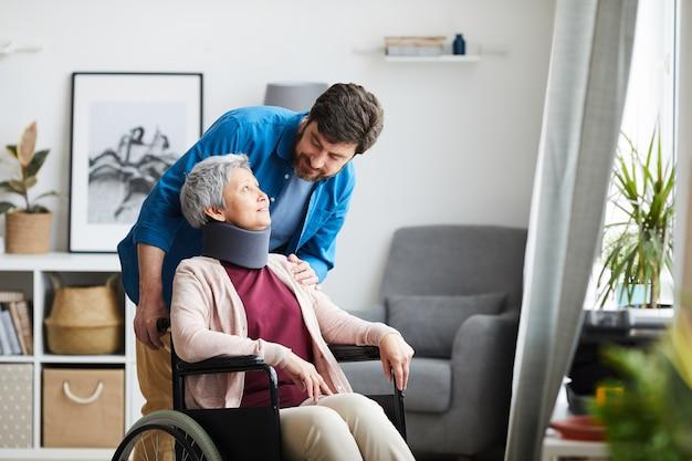 Senior donna con la benda sul collo seduto in sedia a rotelle e parlando con l'uomo nella stanza