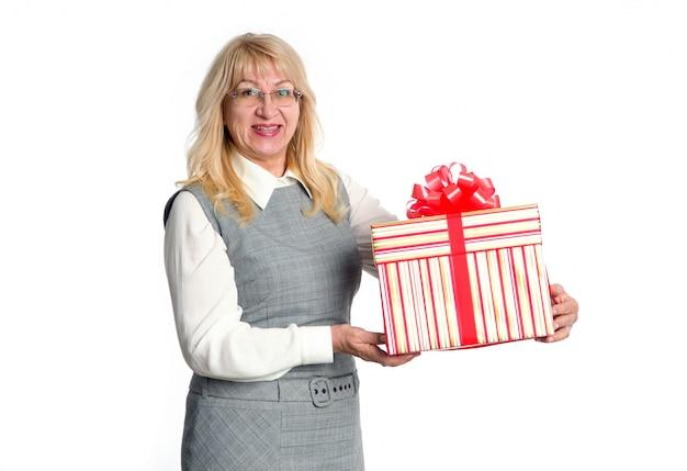 Donna senior con il grande contenitore di regalo a disposizione su un fondo leggero.