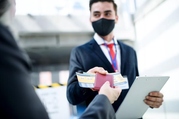 Donna anziana con carta d'imbarco al cancello nel terminal dell'aeroporto coronavirus