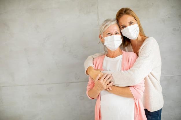 Donna anziana con figlia premurosa a casa che indossa maschere mediche come protezione dal coronavirus
