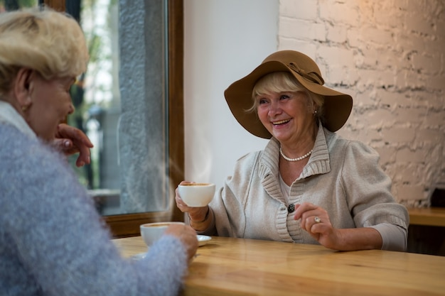 Senior donna con caffè sorridente
