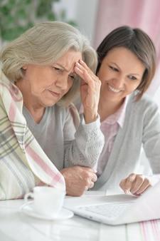 Donna anziana con figlia con laptop e tè