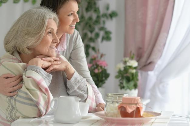 Donna anziana con figlia con tè e cibo