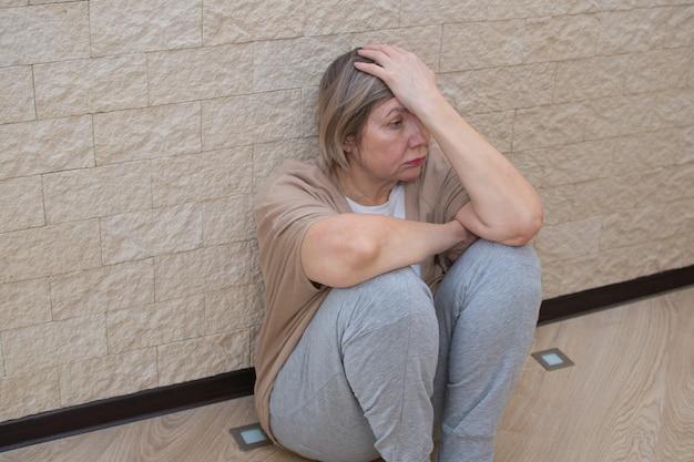 Senior donna con depressione stress triste seduta sul pavimento.