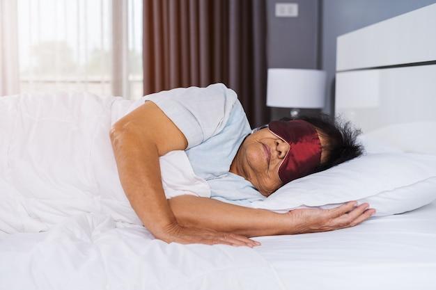 Donna senior con la maschera per gli occhi che dorme su un letto in camera da letto