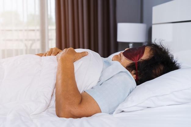 Donna senior con maschera per gli occhi che dorme su un letto