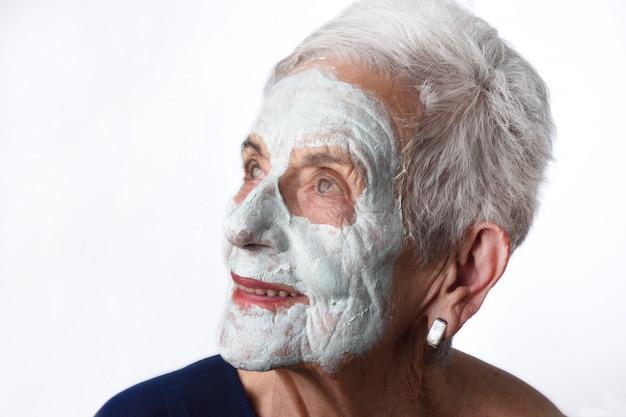 Donna maggiore con la mascherina facian su bianco