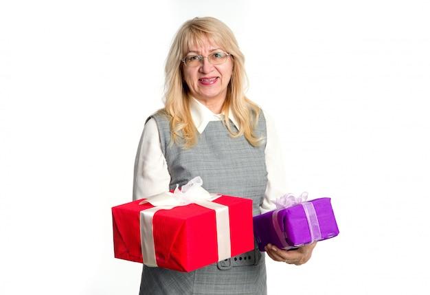Donna senior con i contenitori di regali in sue mani su un fondo leggero.