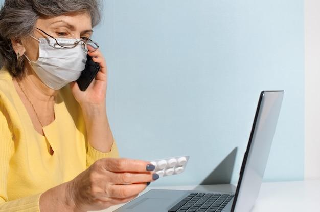 Senior donna con gli occhiali e la maschera medica leggendo le istruzioni per la medicina, copia dello spazio. donna anziana utilizzando laptop a casa. concetto per la consultazione in linea con il medico, nuovo normale.
