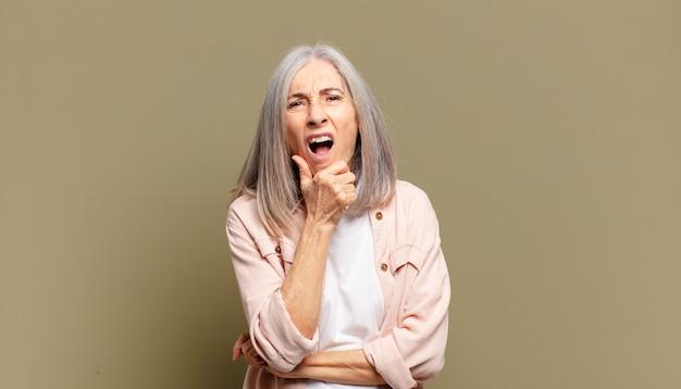 Senior donna con la bocca e gli occhi spalancati e la mano sul mento, sentendosi spiacevolmente scioccata, dicendo cosa o wow