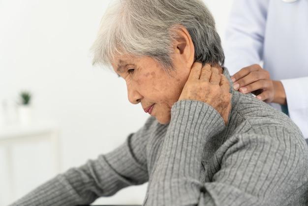Donna senior con dolore al collo nell'ufficio medico, donna senior malata con dolore al collo e alle spalle posteriore sull'articolazione e sul muscolo.