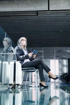 Donna anziana con tablet seduta nella lounge dell'aeroporto, coronavirus, viaggi e nuova normalità.