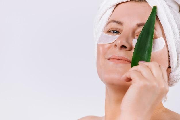 Senior donna con un asciugamano sulla testa che copre gli occhi con una foglia di aloe vera su uno sfondo bianco con spazio laterale vuoto. foto di alta qualità