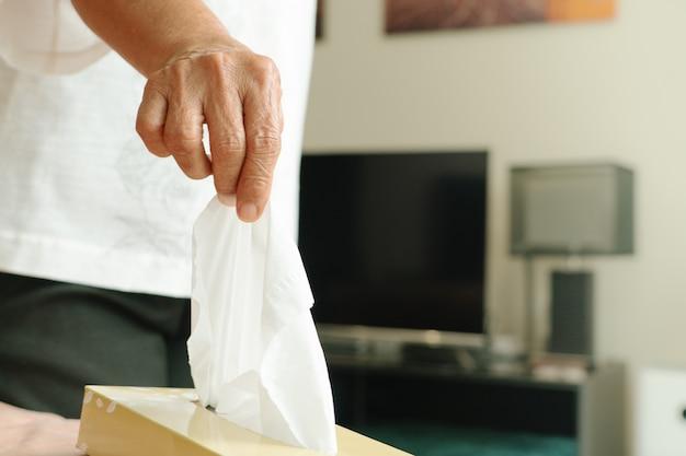 Tovagliolo / carta velina della raccolta manuale delle donne anziane dalla scatola del tessuto