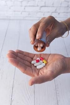 La mano delle donne senior sta prendendo la medicina, fine su.