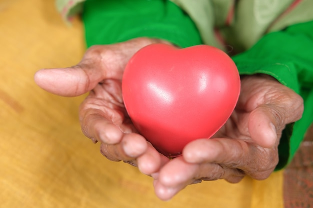 Donne anziane che tengono cuore rosso da vicino