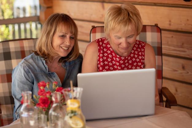 Donne anziane che ridono guardando il laptop mentre sono sedute al tavolo a casa