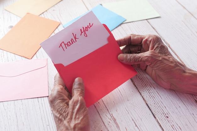 Mano delle donne senior che tiene la lettera di ringraziamento, vista posteriore