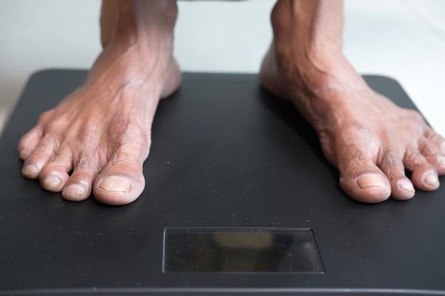 I piedi delle donne senior sulla scala del peso si chiudono su