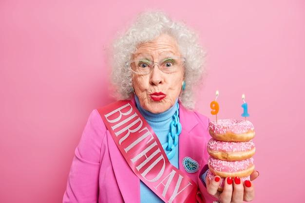 La donna anziana dai capelli grigi rugosa celebra il suo 91esimo compleanno tiene ciambelle con candele, costume elegante e nastro