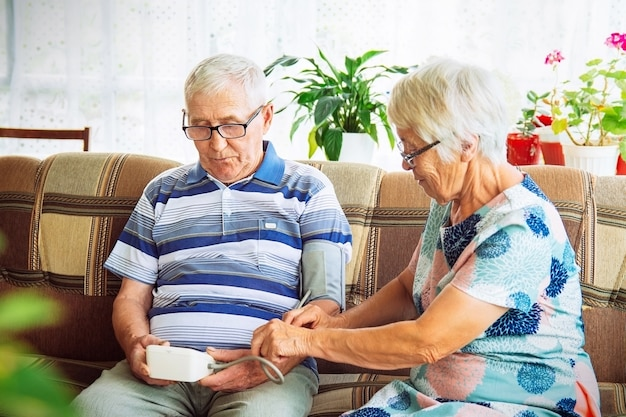 Coppia di anziani seduti sul divano di casa misurando la pressione sanguigna. monitoraggio domiciliare, cura della salute.
