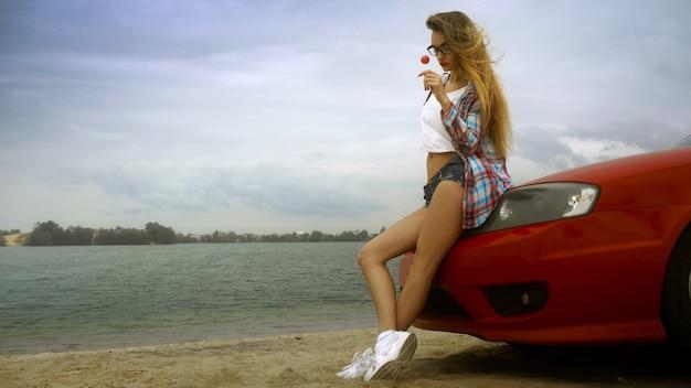 La bionda sensuale con gli occhiali si siede su una macchina rossa con il lecca-lecca in mano in riva al mare