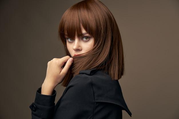 Sensuale bruna aspetto europeo cappotto nero vista ritagliata