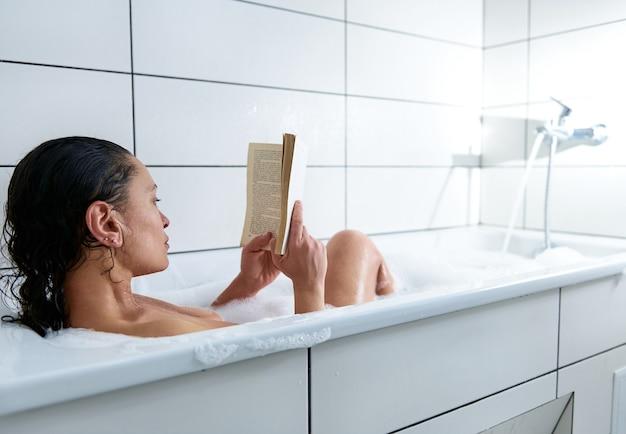 Donna castana sensuale che legge il libro mentre era seduto nella vasca da bagno con schiuma in bagno bianco