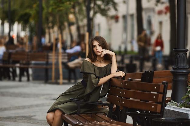 Ragazza sensuale e alla moda modella bruna in abito elegante con spalle nude si siede su una panchina e posa all'aperto presso la strada pedonale