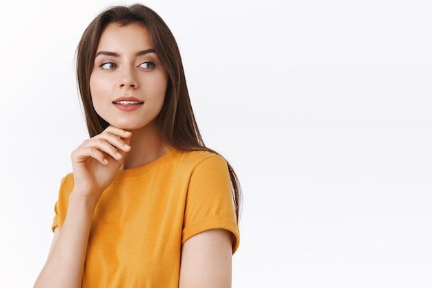 Sensuale, femminile sognante giovane donna bruna in t-shirt gialla voltare le spalle e contemplare qualcosa di bello, bocca aperta toccando il mento civettuolo, in piedi sfondo bianco civettuolo