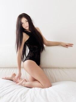 Ragazza sensuale nel letto bianco