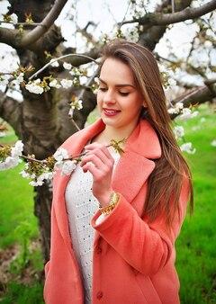 Ritratto sensuale di una donna primaverile, bel viso femminile che si gode i fiori di ciliegio, ragazza sognante con fiori freschi all'aperto, natura stagionale, rami e signora affascinante.