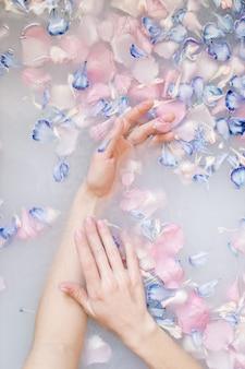 Un ritratto sensuale di una donna in un bagno con latte e fiori trattamenti termali pelle morbida