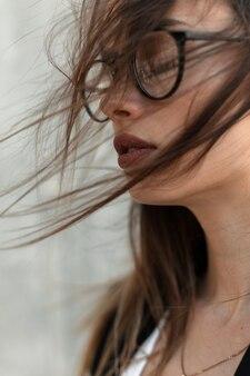 Ritratto sensuale giovane donna attraente con belle labbra con pelle pulita con gli occhi chiusi in occhiali eleganti in vestiti neri di moda godersi il riposo in una giornata ventosa sulla strada. primo piano bel volto femminile.