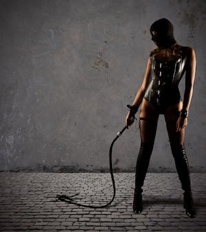 Provocazione sensuale di una donna sexy bdsm in lingerie con frusta
