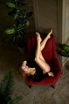 Sensuale donna giovane rossa seducente con gambe sexy nel corpo in posa in interni tropicali.