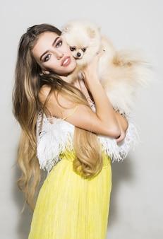 La donna sensuale tiene il piccolo cucciolo sveglio. donna con spitz di pomerania in mano. animale domestico. bellezza e moda. vacanze estive. ragazza in abito giallo con cane che tiene i capelli lunghi.