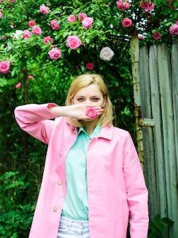 Donna sensuale al parco con rose rosa. bella ragazza in giardino fiorito.