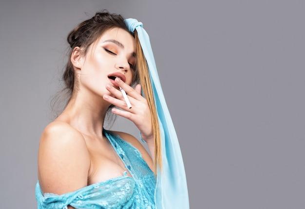Ritratto di donna sensuale. ritratto di alta moda di donna elegante in abito blu. colpo dello studio della donna sensuale su fondo grigio.