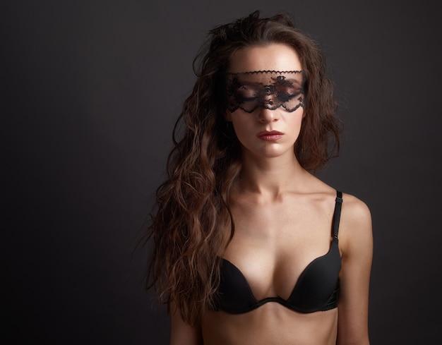 Donna sensuale che posa sopra il fondo scuro con la maschera del pizzo sugli occhi chiusi