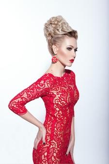 Sensuale donna in abito rosso e jewerly, in piedi con la mano piegata su uno sfondo bianco