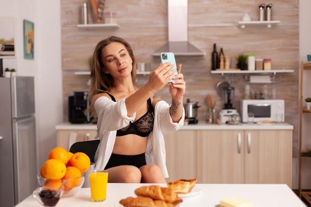 Donna sensuale che scatta foto utilizzando lo smartphone nella cucina di casa mentre indossa biancheria intima sexy