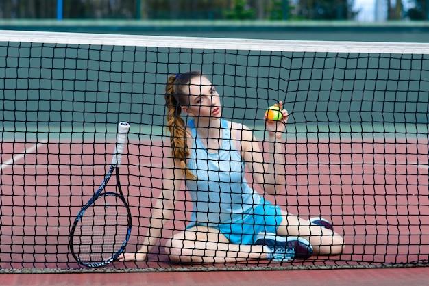 Donna sensuale con la racchetta da tennis in rete sul prato. attività, energia, potere. allenamento di allenamento sportivo. wellness cura del corpo salute