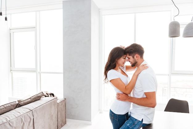 Giovane coppia sensuale in piedi e abbracciata a casa