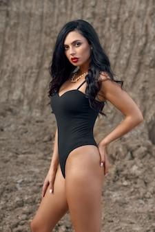 Sensuale giovane donna in tuta nera in posa e che guarda l'obbiettivo all'aperto.