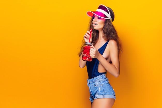 Sensuale giovane donna in abito estivo, tappo che tiene il barattolo con bevanda fresca e stando in piedi sul giallo brillante